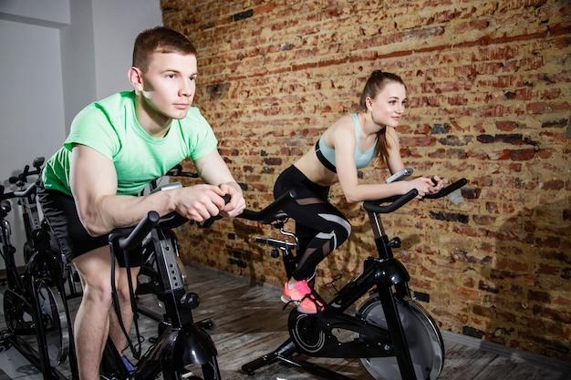 Junger mann und frau, die in die turnhalle, die beine trainierend radfahrenfahrräder des herz trainings radfährt Premium Fotos