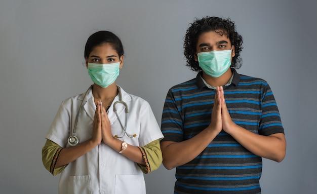 Junger mann und frau, die namaste wegen des ausbruchs von covid-19 tun. neue begrüßung, um die ausbreitung von coronavirus zu vermeiden, anstatt mit einer umarmung oder einem händedruck zu begrüßen. yoga-praxis für das geistige gleichgewicht. Premium Fotos
