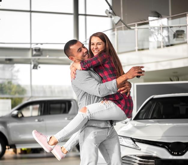 Junger mann und frau feiern neuwagen Premium Fotos