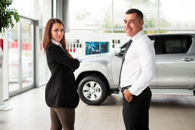 Junger mann und frau im autohaus Kostenlose Fotos