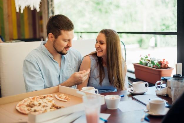 Junger mann und frau verbringen zeit zusammen in der pizzeria Kostenlose Fotos