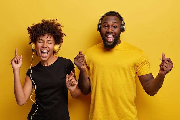 Junger mann und junge frau hören musik in kopfhörern Kostenlose Fotos