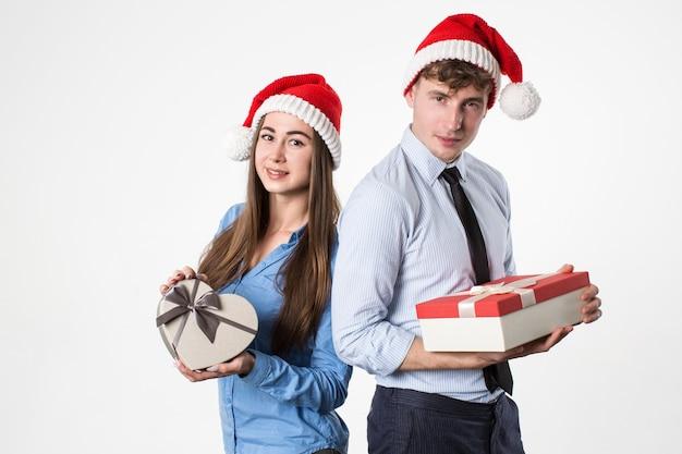 Junger mann und seine freundin in der weihnachtsmütze mit geschenken auf weißem hintergrund. weihnachtsfest. Premium Fotos