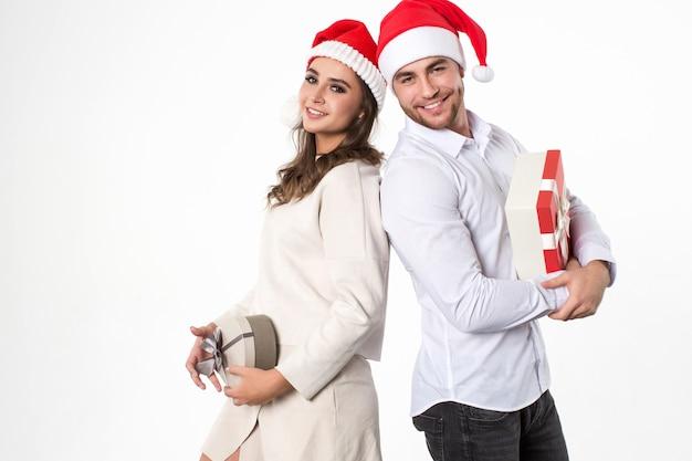 Junger mann und seine freundin mit geschenken auf weißem hintergrund. weihnachtsfest. Premium Fotos