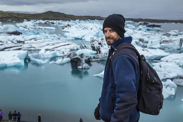 Junger mann vor kleinen blauen eisbergen im jokulsarlon-eissee und sehr grauem himmel in island Kostenlose Fotos