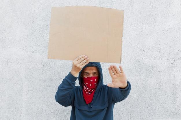 Junger mann winkt handgemachtes kartonplakat mit platz für inschrift Kostenlose Fotos