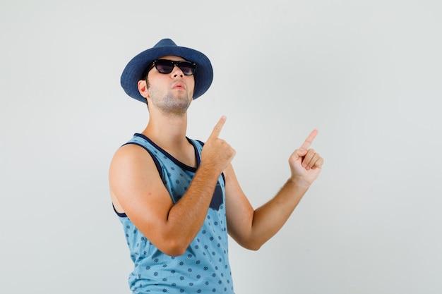 Junger mann zeigt auf die obere rechte ecke im blauen unterhemd, hut und schaut konzentriert. vorderansicht. Kostenlose Fotos