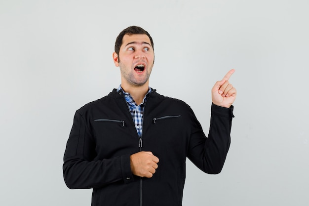 Junger mann zeigt auf die obere rechte ecke in hemd, jacke und schaut hoffnungsvoll, vorderansicht. Kostenlose Fotos