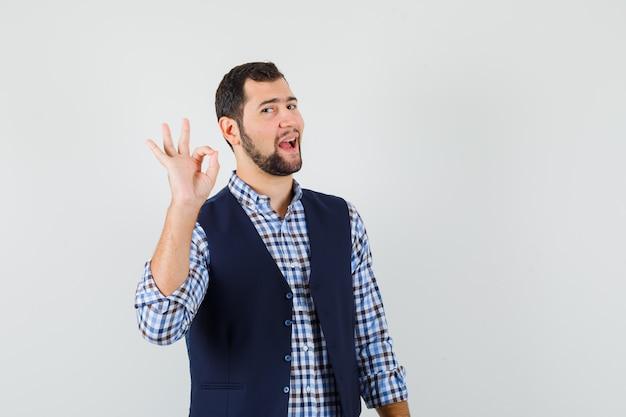 Junger mann zeigt ok geste in hemd, weste und selbstbewusst aussehend. Kostenlose Fotos