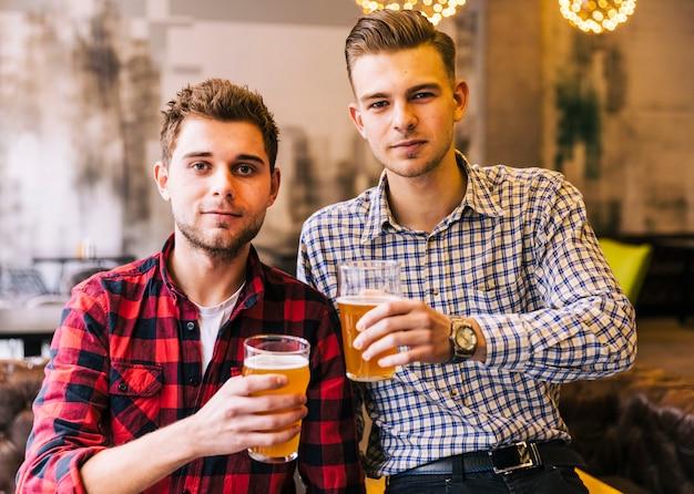 Junger mann zwei, der die gläser bier in der kneipe hält Kostenlose Fotos