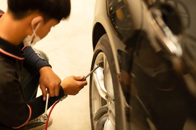 Junger mechaniker, der luftdruck überprüft und luft in den reifen füllt. Premium Fotos
