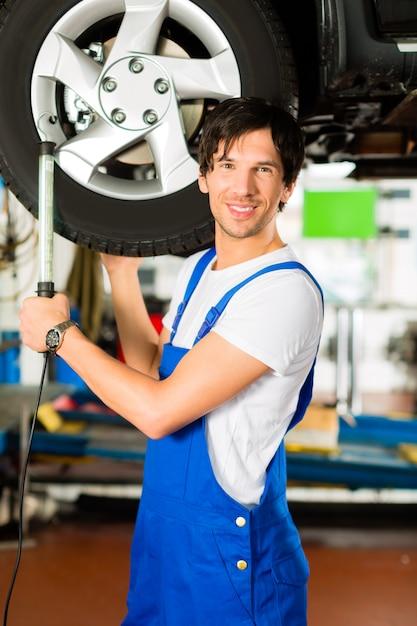 Junger mechaniker im blauen gesamten, der an auto arbeitet Premium Fotos