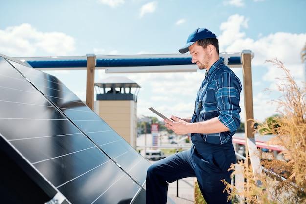 Junger meister mit tablette, der nach online-daten über die installation von sonnenkollektoren sucht, während er auf dem dach steht Premium Fotos