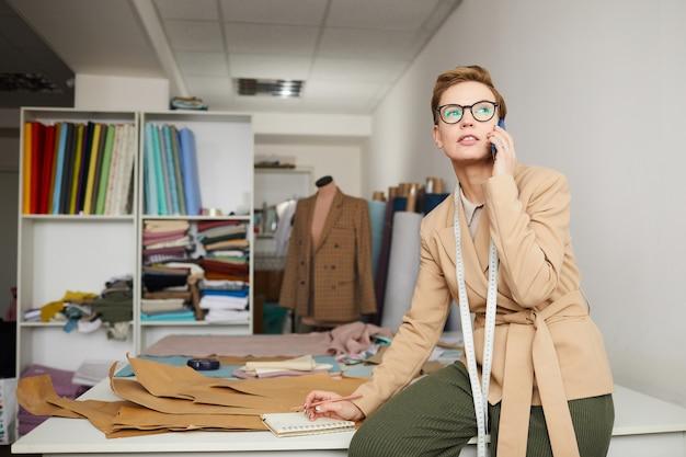 Junger modedesigner, der auf handy spricht, während mit muster in der werkstatt gearbeitet wird Premium Fotos