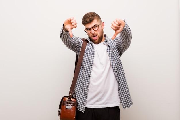 Junger moderner geschäftsmann, der unten daumen zeigt und abneigung ausdrückt. Premium Fotos