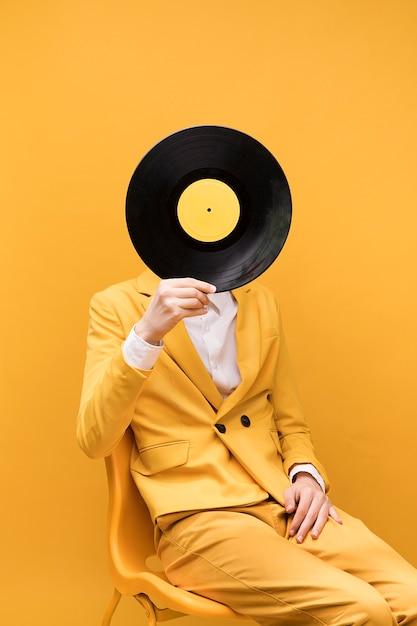 Junger moderner mann, der vinyl vor gesicht hält Kostenlose Fotos