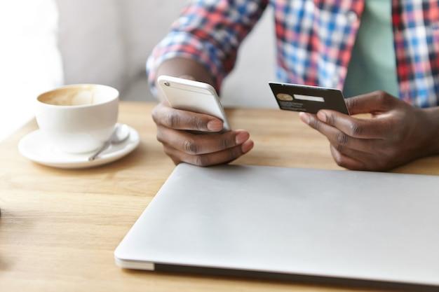 Junger modischer kerl, der an einem café mit smartphone und laptop sitzt Kostenlose Fotos