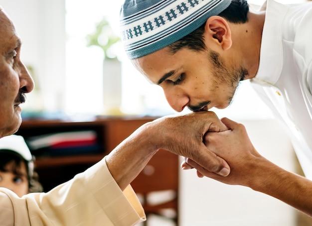 Junger moslemischer mann, der seinem vater respekt zeigt Kostenlose Fotos
