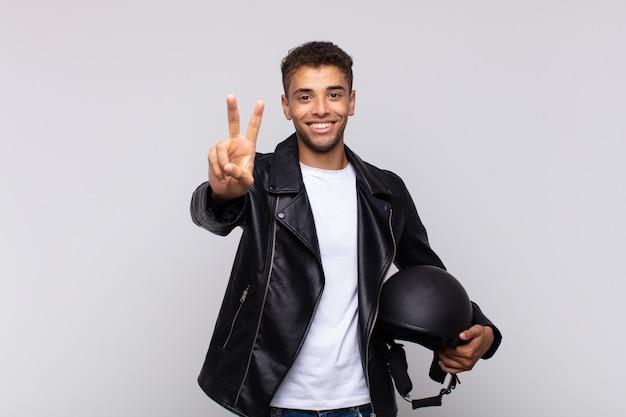 Junger motorradfahrer lächelt und sieht freundlich aus und zeigt nummer zwei oder sekunde mit der hand nach vorne Premium Fotos