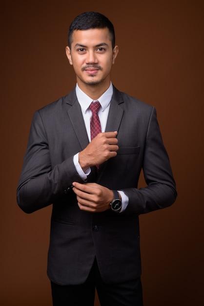 Junger multiethnischer asiatischer geschäftsmann gegen braune wand Premium Fotos