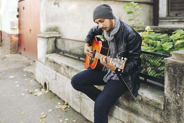 Junger musiker mit gitarre in der stadt Kostenlose Fotos