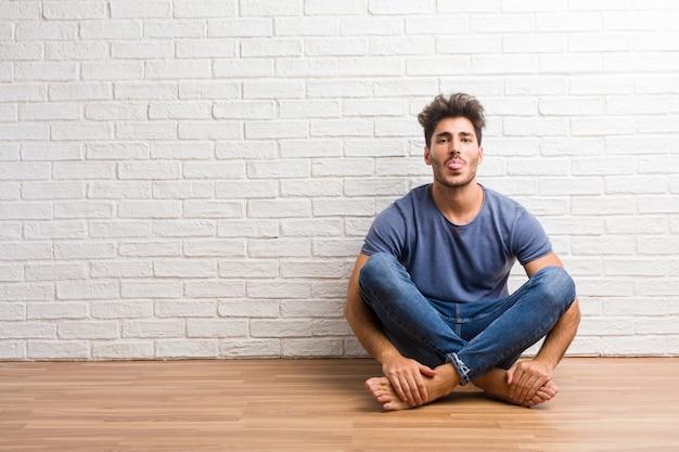 Junger natürlicher mann sitzen auf einem bretterbodenausdruck des vertrauens und des gefühls Premium Fotos
