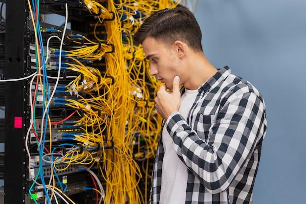 Junger netzingenieur auf mittlerem schuss des serverraumes Kostenlose Fotos