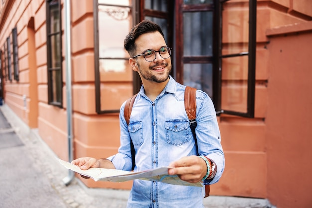 Junger niedlicher hipster, der in einer alten stadt steht, karte hält und die ansicht genießt. Premium Fotos