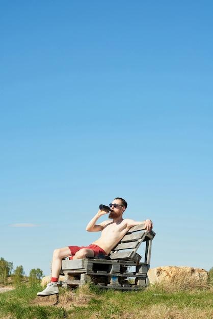 Junger oben ohne bärtiger mann, der bier trinkt, während auf hölzerner bank draußen auf klarem blauem himmelhintergrund sitzt Premium Fotos