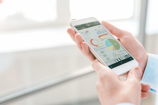 Junger ökonom oder finanzanalyst, der smartphone mit diagrammen und diagrammen auf seinem bildschirm hält, während sie sie analysieren Premium Fotos
