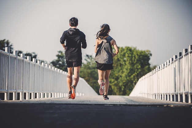 Junger paarläufer, der auf laufender straße im stadtpark läuft Premium Fotos