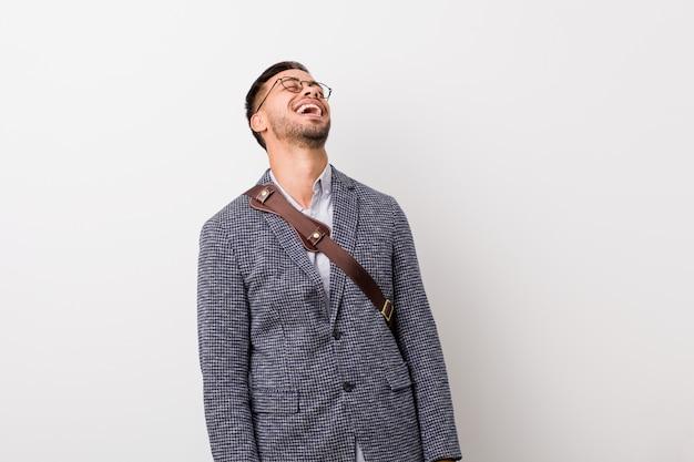 Junger philippinischer geschäftsmann gegen eine weiße wand entspannte sich und das glückliche lachen, der ausgedehnte hals, der zähne zeigt. Premium Fotos