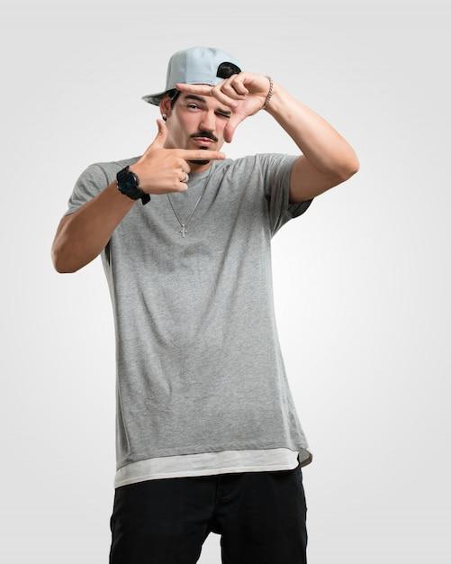 Junger rapper-mann, der eine rahmenform mit den händen macht und versucht, sich zu konzentrieren, als ob es eine kamera wäre Premium Fotos