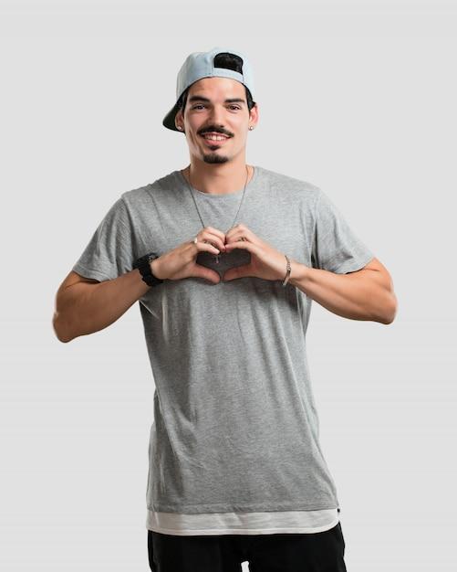Junger rappermann, der ein herz mit den händen macht und das konzept der liebe und der freundschaft, glücklich und lächeln ausdrückt Premium Fotos