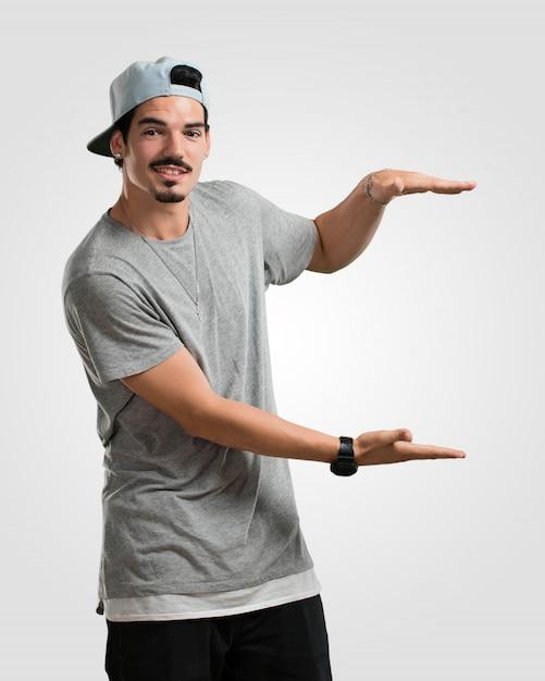Junger rappermann, der etwas mit den händen hält, ein produkt zeigt, lächelt und nett und bietet einen eingebildeten gegenstand an Premium Fotos
