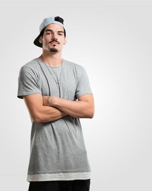 Junger rappermann, der seine arme kreuzt, ernst und imposant, sich überzeugt und leistung zeigend Premium Fotos