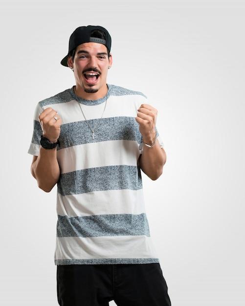 Junger rappermann sehr glücklich und aufgeregt, arme anheben, einen sieg oder einen erfolg feiern und die lotterie gewinnen Premium Fotos