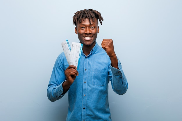 Junger rasta schwarzer mann, der die flugtickets halten, die faust, aggressiven gesichtsausdruck zeigen. Premium Fotos