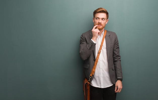 Junger redheadgeschäftsmann zweifelnd und verwirrt Premium Fotos