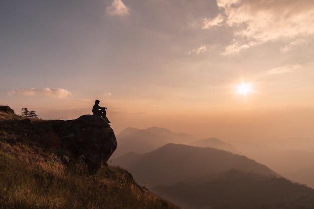 Junger reisender, der schöne landschaft auf berg, abenteuerreiselebensstilkonzept sich entspannt und schaut Premium Fotos