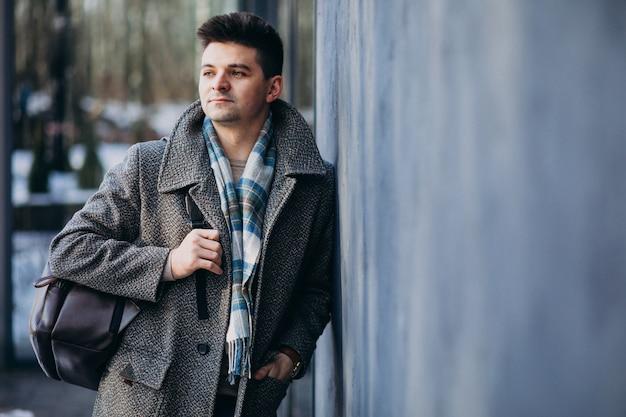 Junger reisender des gutaussehenden mannes, der draußen telefon verwendet Kostenlose Fotos