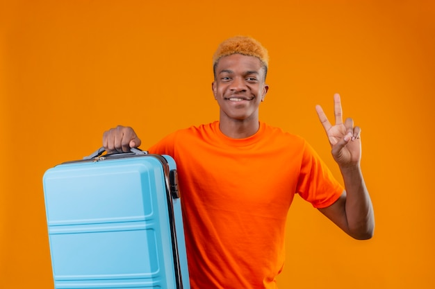 Junger reisender junge, der das orange t-shirt hält, das den lächelnden koffer hält und nummer zwei oder siegeszeichen zeigt, das über orange wand steht Kostenlose Fotos
