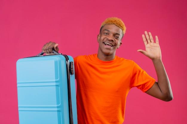 Junger reisender junge, der orange t-shirt hält koffer hält lächelnd fröhlich winkend mit hand steht über rosa wand Kostenlose Fotos