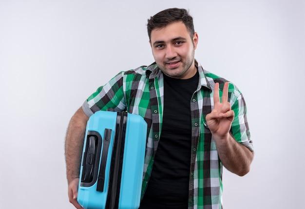 Junger reisender mann im karierten hemd, das den koffer hält und mit dem finger nummer zwei zeigt, der lächelnd über weißer wand steht Kostenlose Fotos