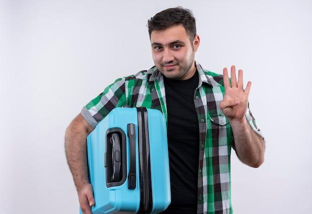 Junger reisender mann im karierten hemd, das den lächelnden koffer hält und mit den fingern nummer vier zeigt, die über weißer wand stehen Kostenlose Fotos