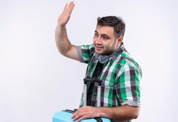 Junger reisender mann im karierten hemd, das koffer hält, der lächelnd winkend mit der hand steht steht über weißer wand Kostenlose Fotos