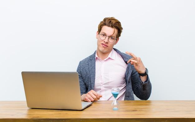 Junger roter hauptgeschäftsmann, der in seinem schreibtisch mit einer uhr arbeitet. zeitkonzept Premium Fotos