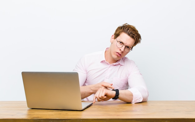 Junger roter hauptgeschäftsmann, der in seinem schreibtisch mit einer uhr arbeitet Premium Fotos