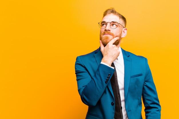 Junger roter hauptgeschäftsmann, der nachdenklich sich fühlt, ideen sich wundert oder sich vorstellt, oben träumt und schaut, um raum zu kopieren Premium Fotos