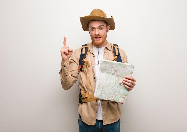 Junger rothaarigeforschermann, der eine großartige idee, konzept der kreativität hat. hält eine karte. Premium Fotos